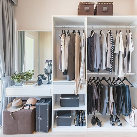 white wardobe and dressing table with clothes hanging in walk in closet