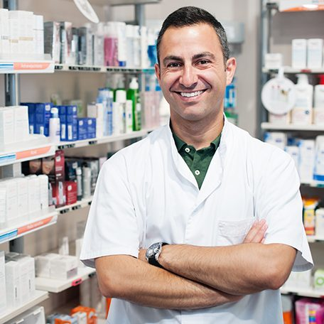 cheerful smiling pharmacist chemist man standing in pharmacy