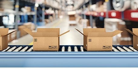 Cardboard boxes on conveyor roller with racks on background