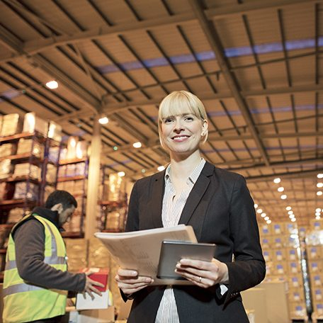Businesswoman with folder and tablet computer in warehouse