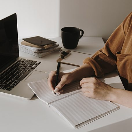 Minimalist home office workspace with laptop, coffee cup, clipboard. Woman write in a paper sheet notebook. Morning work, business concept. Sunlight shadows on the wall.